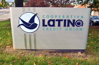 Beautiful sign marks the site of the Latino Community Credit Union. Photo by Liz Hannah