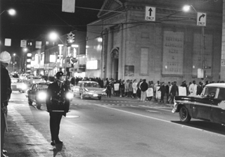 Students from North Carolina College march double-file to the site of the protest, watched over by police officers. Photo by Bill Boyarsky
